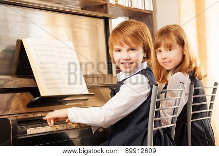 Cheerful beautiful small girls play piano together