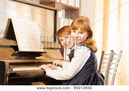 Two cute small girls in uniforms playing piano
