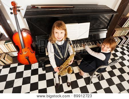 View from top of girls play on music instruments
