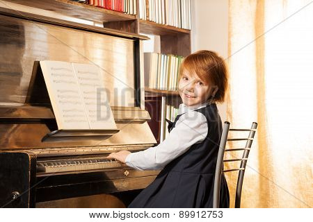 Beautiful small girl with short hair playing piano