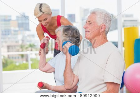 Senior man lifting dumbbells while trainer assisting woman in background at gym