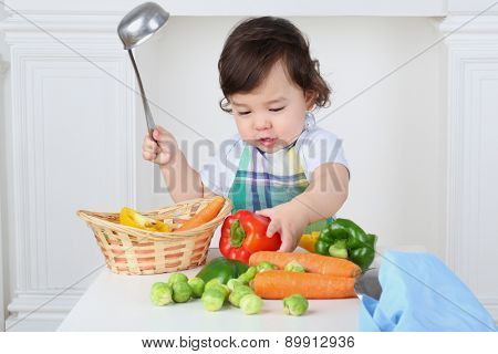 Small boy in kitchen apron with ladle and vegetables at table