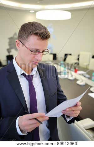 Portrait of businessman reading a document in the conference hall