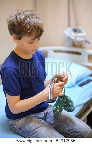 Boy sitting on a bed and holding a special cap for electroencephalography