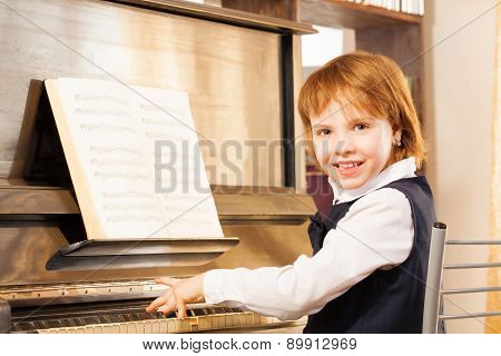 Happy girl with short hair playing the piano