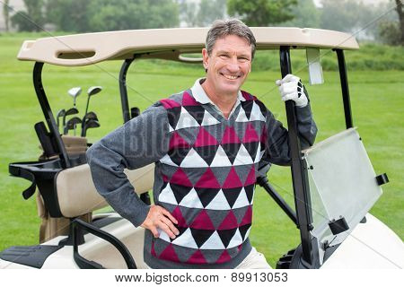Happy golfer beside his golf buggy on a sunny day at the golf course