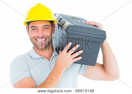 Portrait of confident handyman carrying toolbox on shoulder over white background