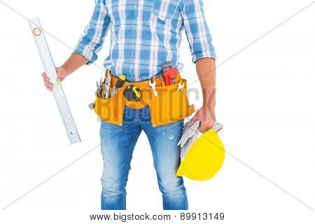 Midsection of manual worker holding spirit level on white background