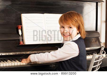 Happy small girl in school uniform plays piano