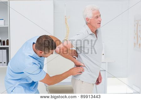 Physiotherapist giving back massage to senior man in clinic