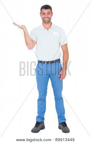 Full length portrait of smiling salesman presenting in his palm against white background