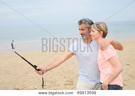 Couple taking picture with smartphone and extendable monopod