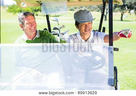 Golfing friends driving in their golf buggy at the golf course