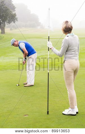 Lady golfer holding flag for partner putting ball on a foggy day at the golf course
