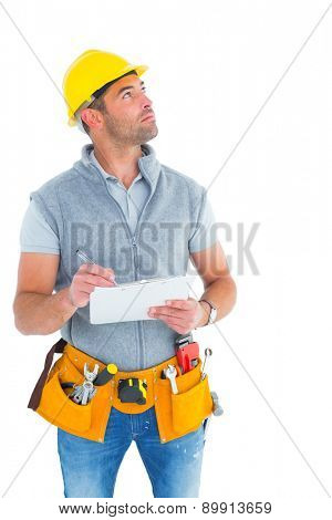 Manual worker looking up while writing on clipboard over white background