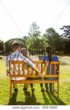 Man being unfaithful in the park on a sunny day on a sunny day
