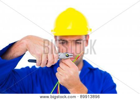 Male electrician wearing hard hat while cutting wire with pliers over white background
