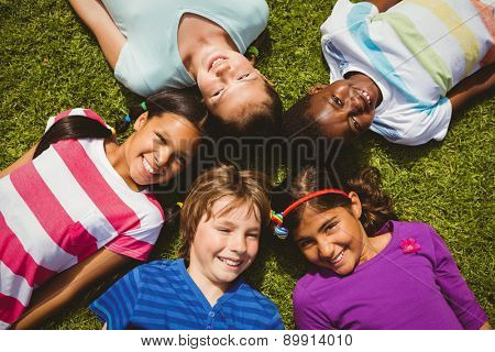 High angle portrait of children lying on grass at the park