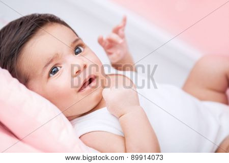 Cute little baby portrait, sweet adorable newborn child lying down on bed at home, healthy lifestyle, happy childhood concept