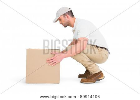 Delivery man crouching while picking cardboard box on white background