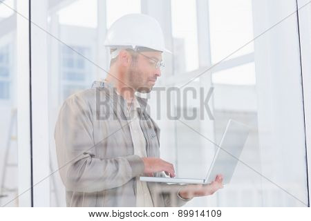 Male architect using laptop in office