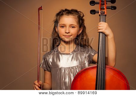 Smiling girl holding string to play violoncello