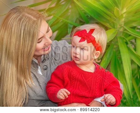 Portrait of beautiful blond female with her little daughter having fun in the park, enjoying motherhood, love and happiness concept