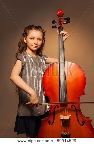Classy girl with long hair holding cello to play