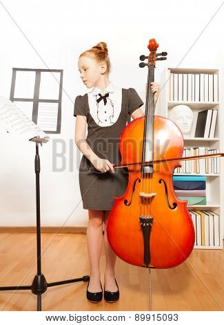 Beautiful girl holds cello looking at musical note