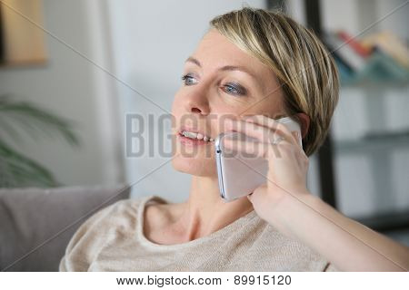 Woman relaxing in sofa talking on mobilephone