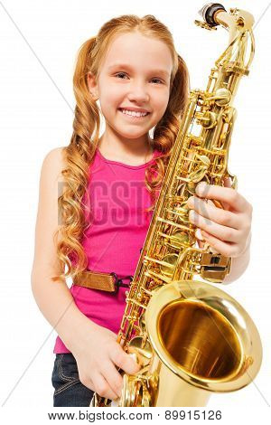 Portrait of happy girl playing alto saxophone