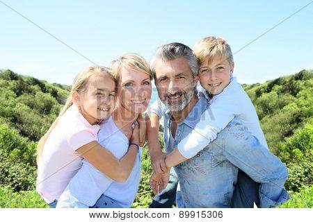 Parents giving piggyback ride to kids