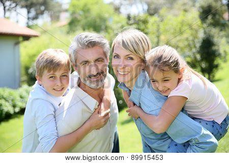 Parents giving piggyback ride to kids in garden