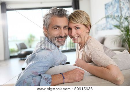 Middle-aged couple relaxing in sofa at home