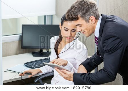 Manager and female customer service agent using tablet computer together in office