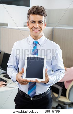 Portrait of confident male manager holding tablet computer at call center