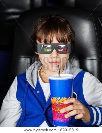 Girl wearing 3D glasses while having drink in cinema theater