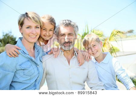 Happy family standing in home private garden