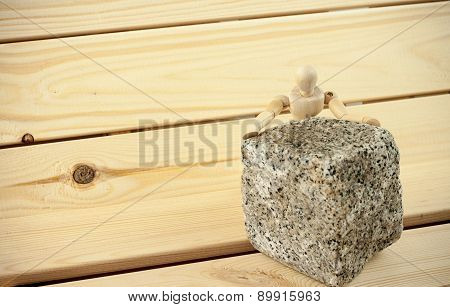 Wooden human model figure behind granite paving block