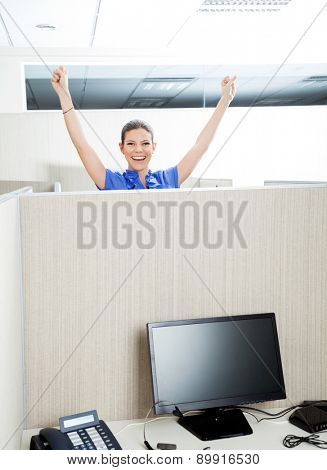 Portrait of female successful customer service representative with arms raised in cubicle