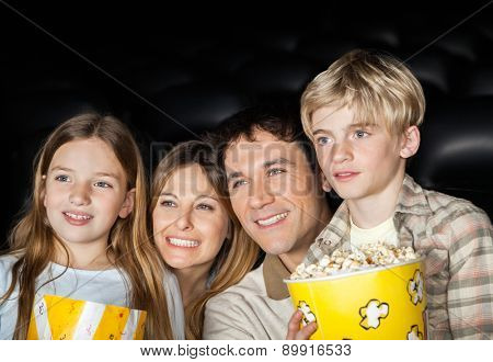 Happy family of four holding popcorn while watching film in movie theater