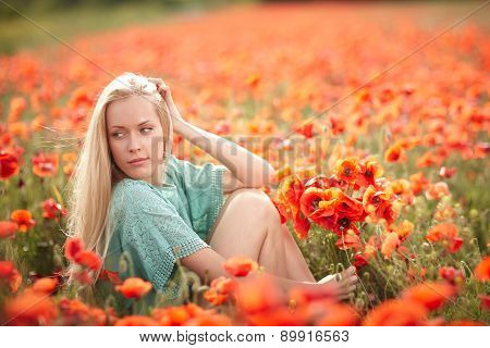 Beautiful woman on poppy flower field