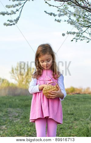 Adorable young girl holds an small basket