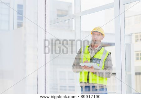 Male supervisor in reflective clothing writing on clipboard in office