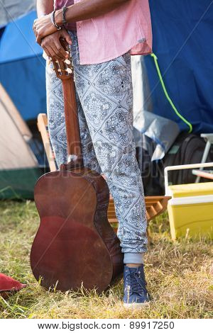 Hipster holding guitar at campsite on a sunny day