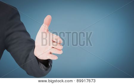 Businessman extending arm for handshake against blue