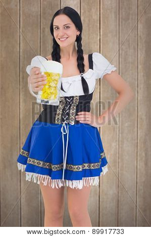 Pretty oktoberfest girl holding beer tankard against wooden surface with planks