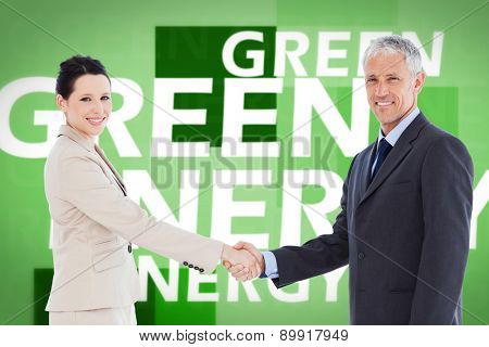 Smiling business people shaking hands while looking at the camera against creative image of green energy concept
