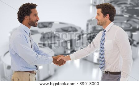 Smiling young businessmen shaking hands in office against cogs and wheels