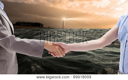 Handshake between two women against stormy sea with lighthouse